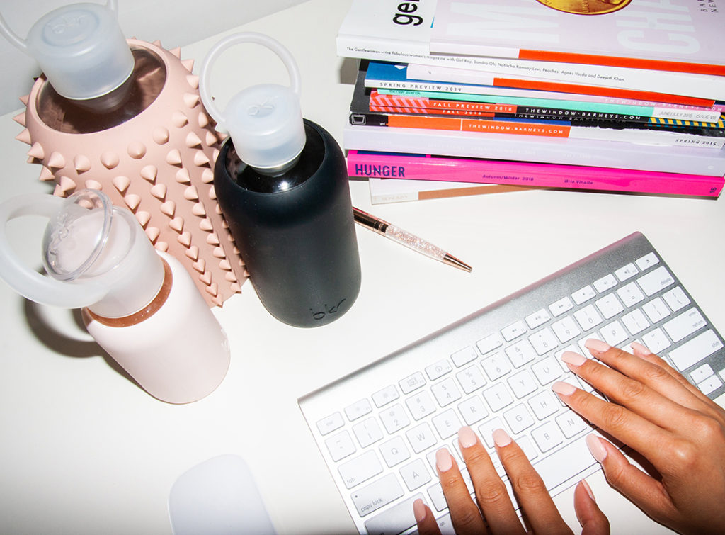desk set-up with bkr water bottles and magazines