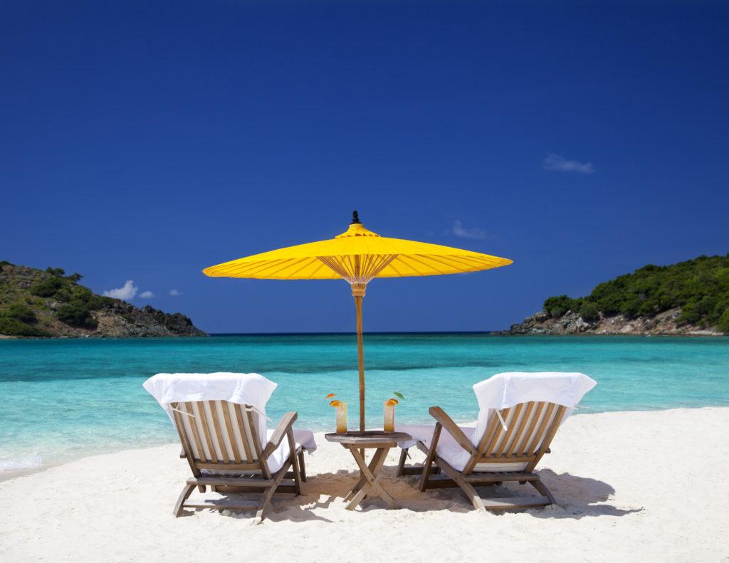 beach chairs under a yellow umbrella