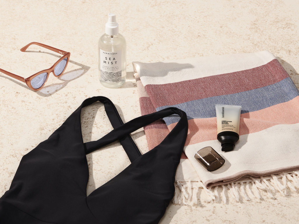 Beach essentials with summersalt swimsuit, sunglasses, herbivore botanical sea mist, complexion rescue defense and minna towel