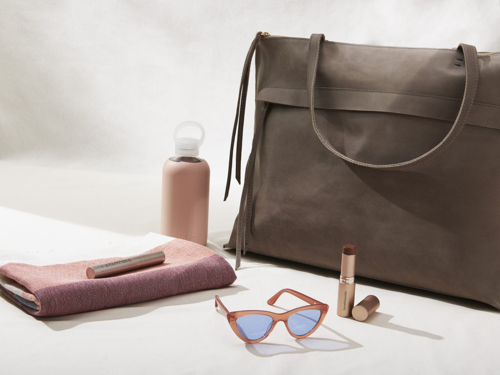 Weekender bag with bkr water bottle, sunglasses, bareminerals makeup and minna towel.