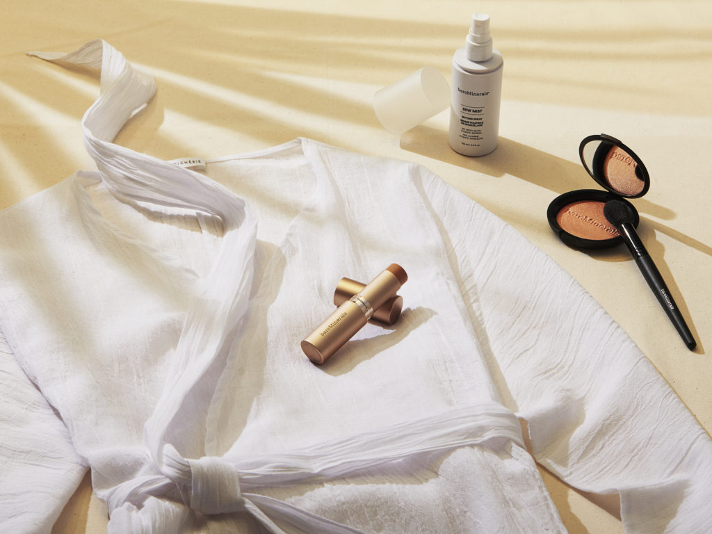 Post-beach essentials including swimsuit coverup, dew mist setting spray, endless glow highlighter and complexion rescue foundation stick.