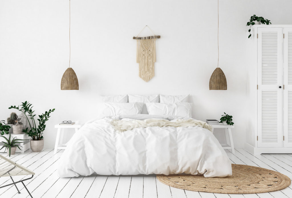 bedroom with crisp white linens, plants and a natural jute rug