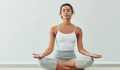 woman meditating on a yoga mat against a grey background