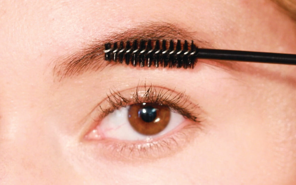 brushing serum through eyebrows with a spoolie brush