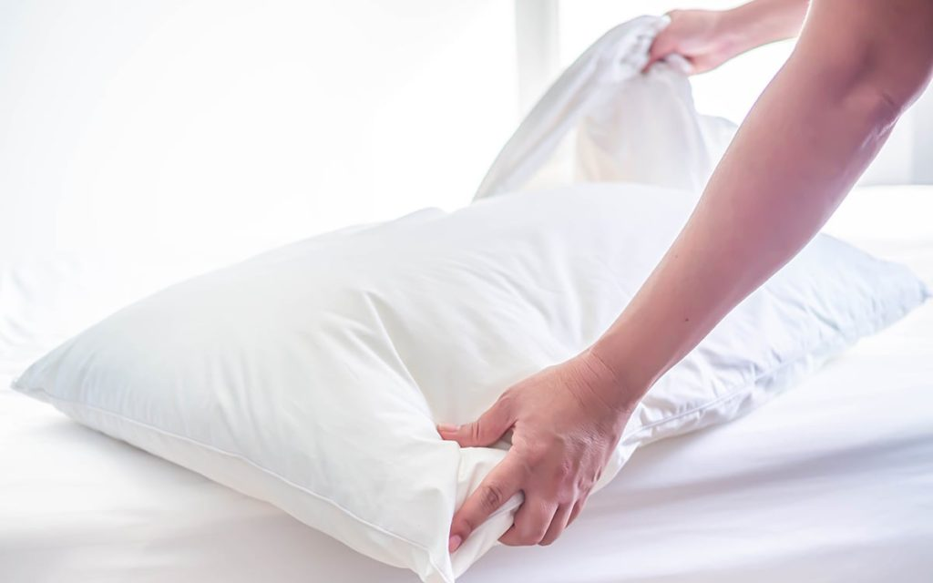 Person changing white pillow case
